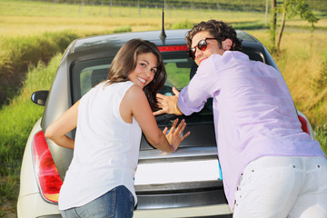 Smiling and funny couple pushing a car