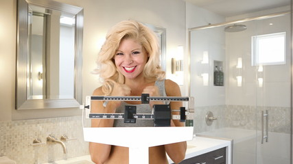 Closeup of happy young woman weighing self on scales