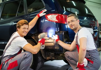 Two workers choosing correct shade in a car body workshop