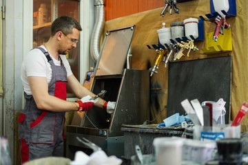 Serviceman cleaning airbrush gun in a car body workshop