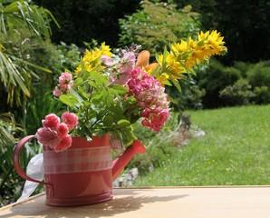 Gießkanne mit Sommerblumen im Garten