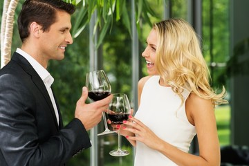 Cheerful couple with glasses of red wine talking