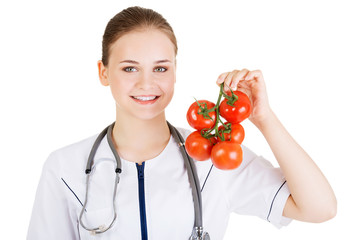 Female doctor holding healthy tomatoes.