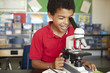Boy in science class with microscope - 66527691