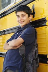 Pre teen boy with school bus