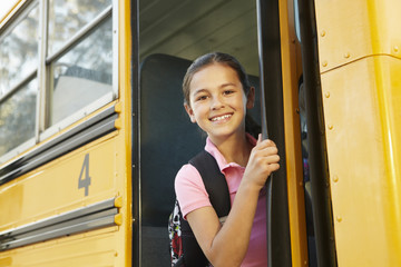Pre teen girl getting on school bus