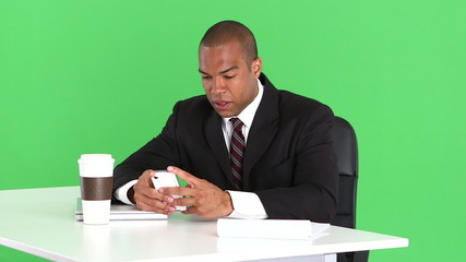 Male executive at desk with cell phone