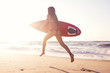 Hot surfer girl running in the beach with her surfboard