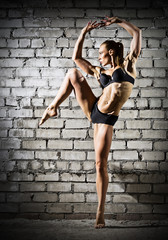Muscular dancing woman on brick wall (dark version)