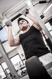 Young man training in the gym. Filtered image.