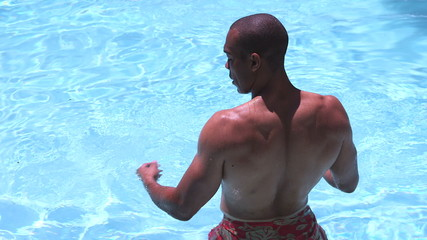 African American man standing in swimming pool