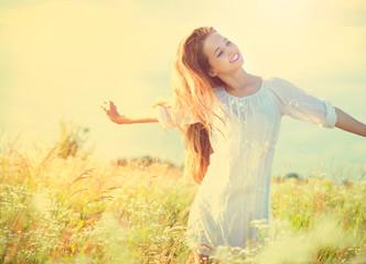 Beauty model girl in white dress having fun on summer field