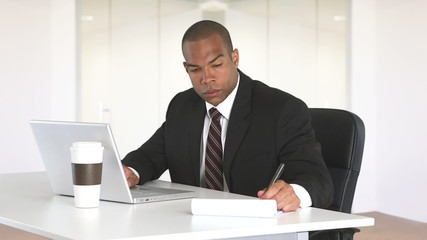Smiling man using laptop at desk