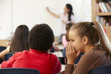 Schoolchildren whispering in class