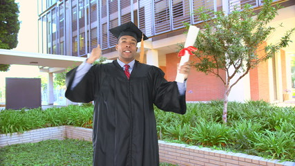African American man with graduation gown kissing diploma