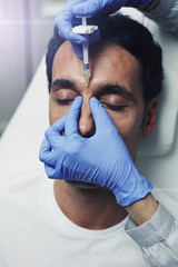 Young attractive man receiving collagen injection
