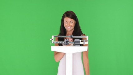 Young woman happily weighing herself on a scale