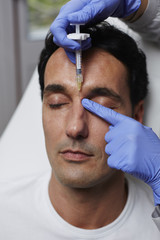 Plastic surgeon giving cosmetic injection in male skin