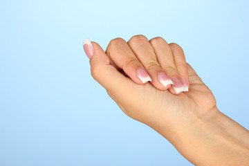 Beautiful woman's hand with french manicure on blue background