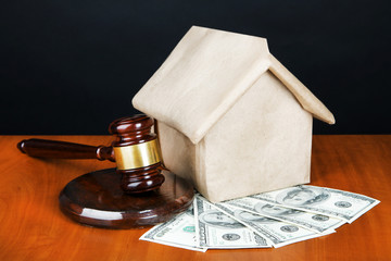 Gavel,model of house and money on table on black background