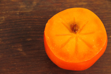 Half persimmon on wooden background