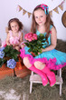 Beautiful small girls in petty skirts holding flowers