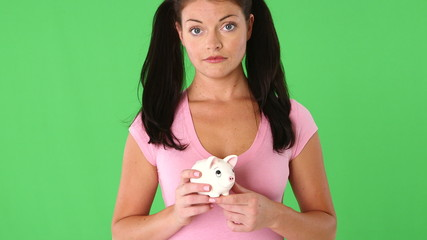 Portrait of young woman holding a piggy bank and hammer