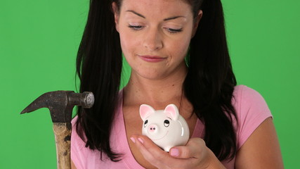 Closeup portrait of young woman breaking piggy bank with hammer