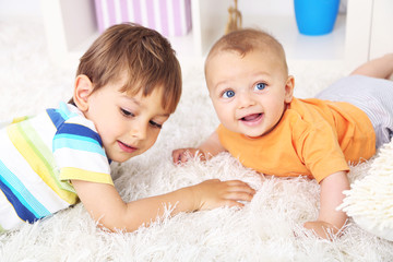 Cute little boys lying on carpet