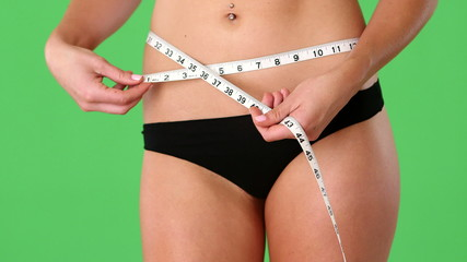 Woman with measuring tape at waist