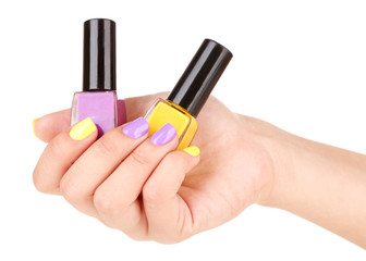 Female hand with stylish colorful nails holding bottle with