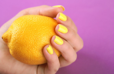 Female hand with stylish colorful nails holding fresh lemon,