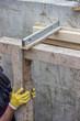 worker adjust level of wooden framework installation