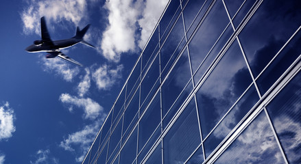 Airliner flying over high office buildings