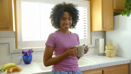 Woman drinking morning coffee in the kitchen