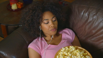 Woman lying on couch eating popcorn and listening to music