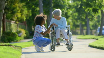 Nurse walking with elderly woman in wheelchair