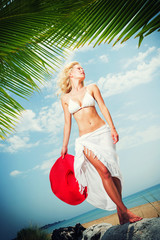 Young woman in white bikini holding sarong on the beach