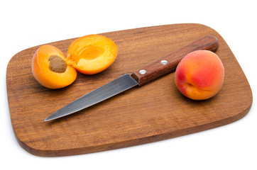 Apricots and a knife on a wooden cutting board