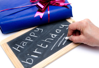 Happy birthday written on a slate blackboard with a gift
