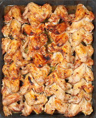 many roasted spicy chicken wings on hot tray