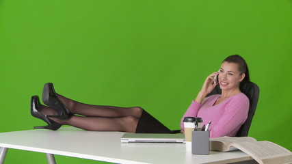 Young business woman relaxing with feet up on desk and talking o