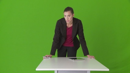 Serious young businesswoman executive leaning on desk