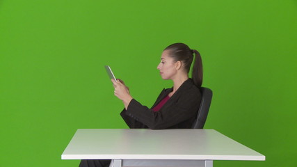 Young businesswoman at desk using touchscreen