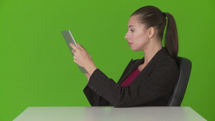 Closeup of young businesswoman at desk using touchscreen