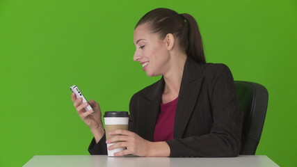 Young businesswoman using cellphone at desk