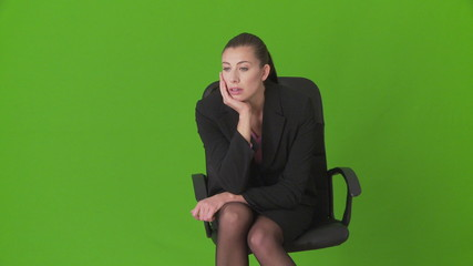 Serious young businesswoman sitting in office chair thinking
