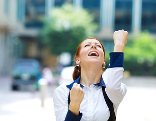 Businesswoman celebrating success pumping up fists