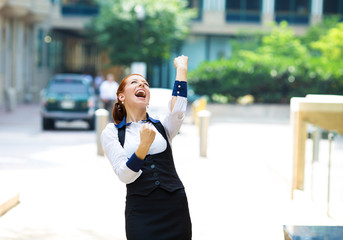 Businesswoman celebrating success outside corporate office