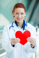 Female doctor, health care professional holding red heart